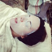Client after a facial enjoying a refreshing collagen mask.